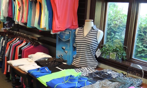 Women's golf attire by the store window.